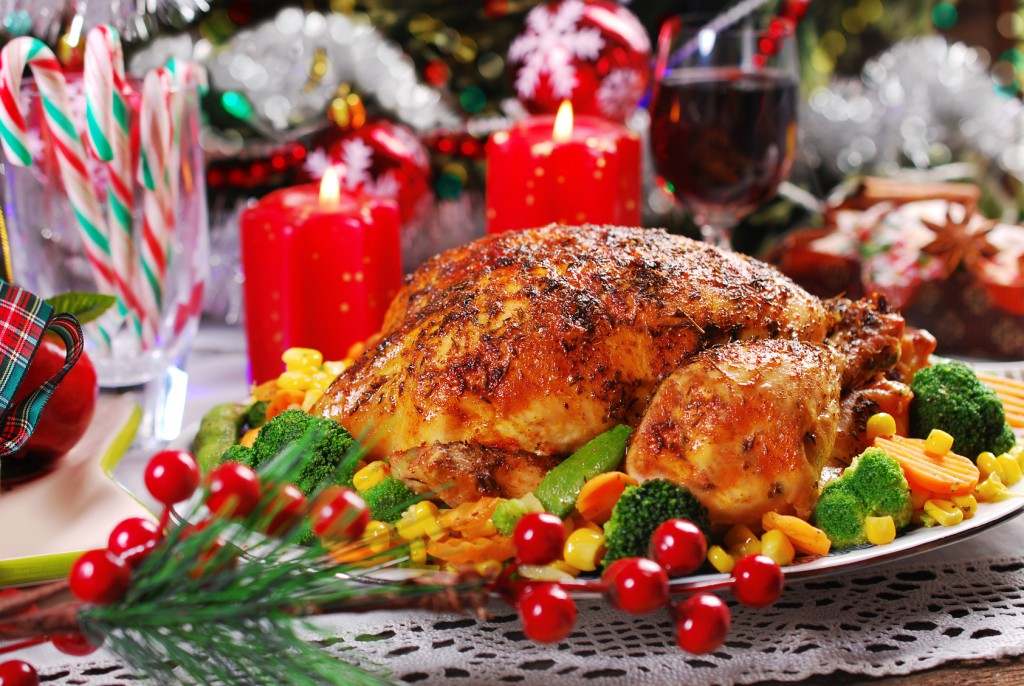 roasted whole chicken with colorful vegetables on christmas table