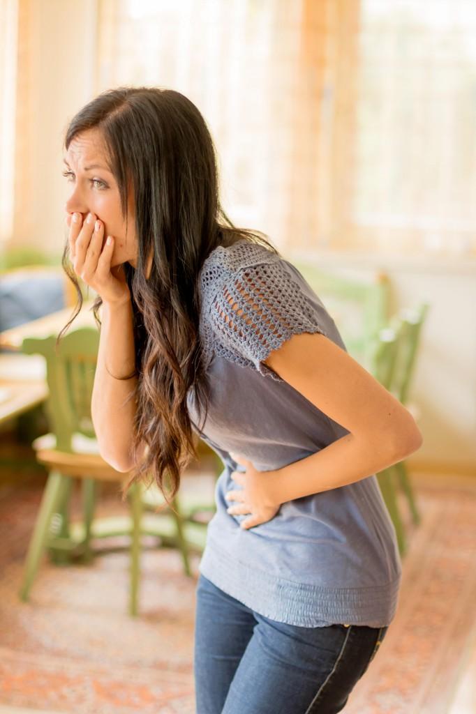 Eine junge Frau hat Schmerzen im Bauch