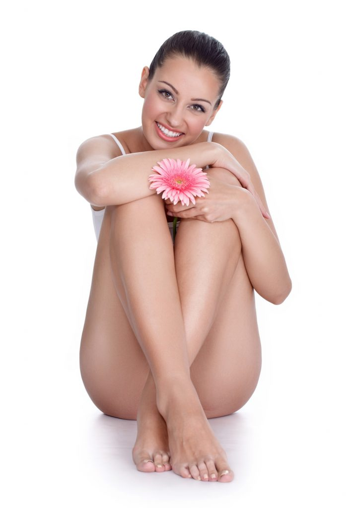 Young beautiful woman with flower siting on floor