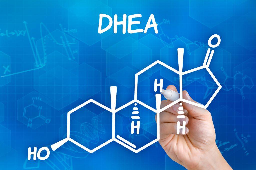 Hand mit Stift zeichnet chemische Strukturformel von DHEA